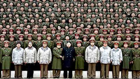 Kim Jong-Un stands with his army behind him.