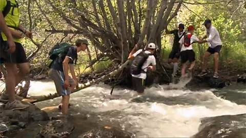 Teenagers help each other cross a swift-moving stream. thumbnail