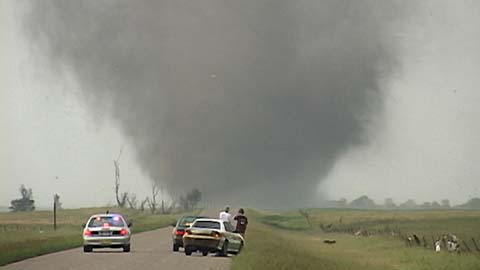 People stopped on rural road observing twister in distance thumbnail